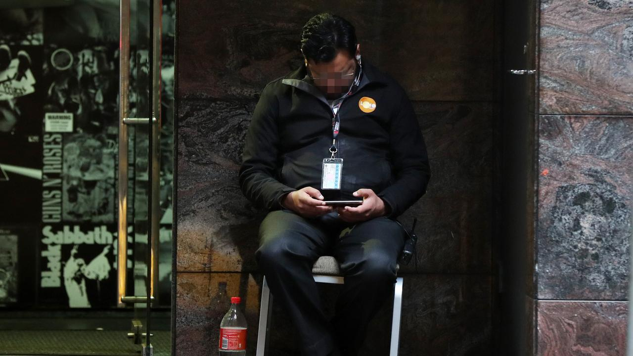 A security guard watching a video on his phone outside the Adina Apartment Hotel near Town Hall. Picture: Jonathan Ng