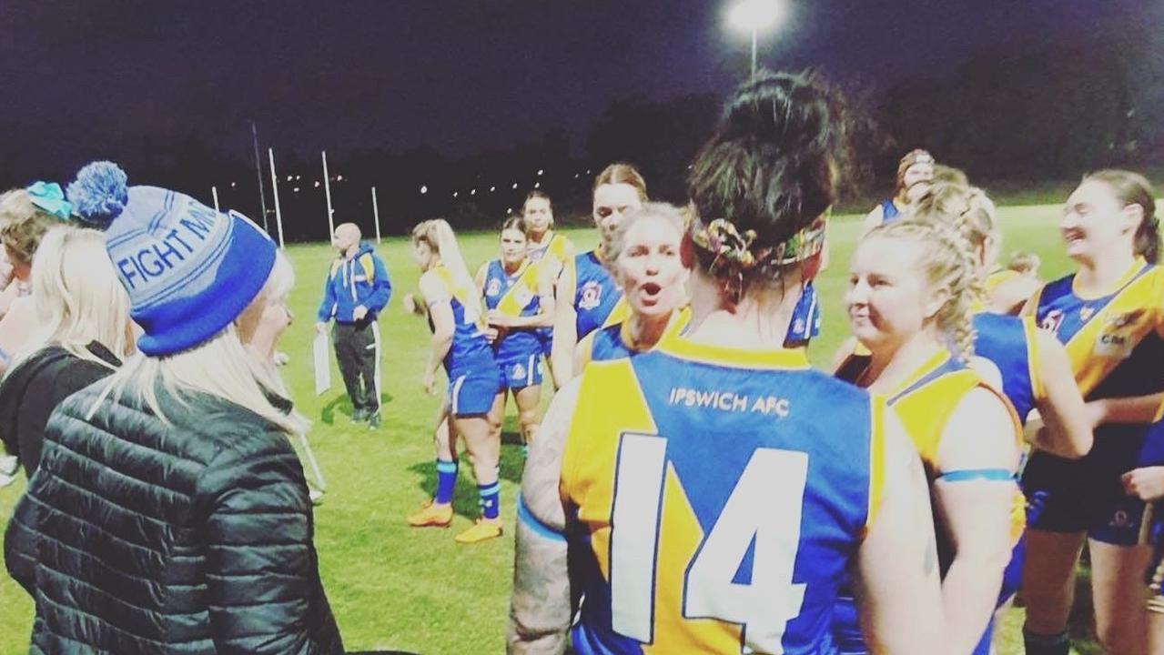 Ipswich Eagles footballers rally around teammate Lara Boon (number 14) and her mum Jo (wearing a special beanie). Jo, a former caring nurse, has been diagnosed with motor neurone disease.
