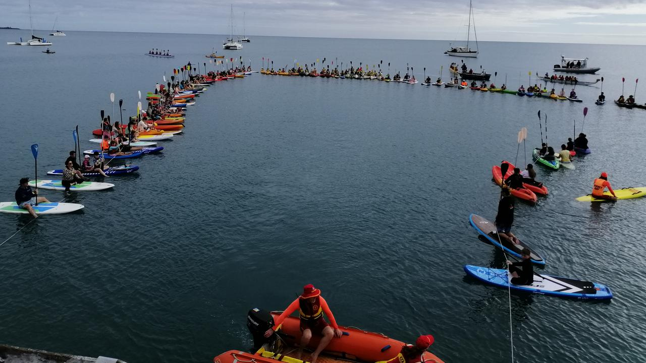 Participants gather on the water near Torquay pier for Paddle Out For Whales 2020.