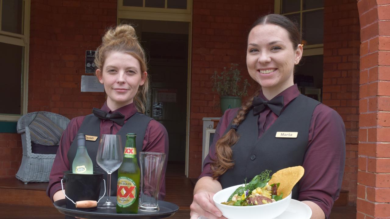 Portside staff (L) Taylah Berry and Marta Hackett display drinks and paella con pollo. Photo: Stuart Fast