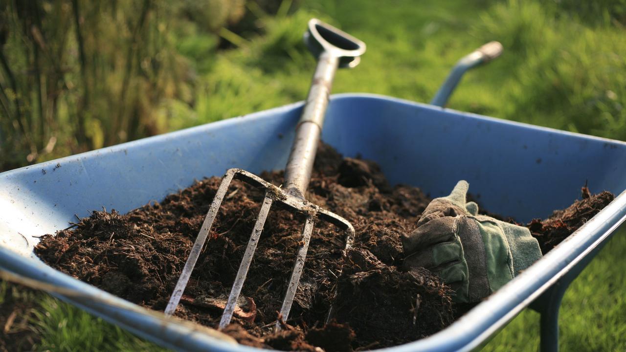 The Organic Kitchen Gardener generic image. Soil, gardening gloves and rake in wheelbarrow.