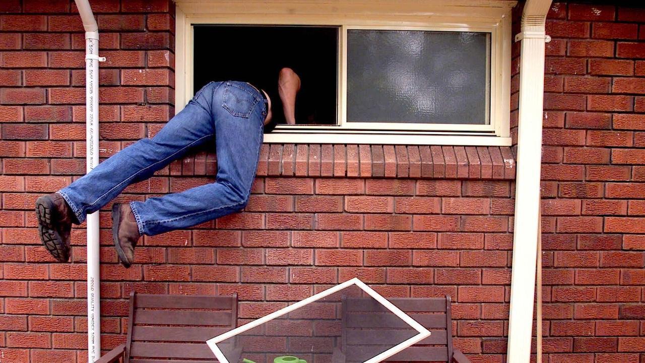 Generic photograph of a burglar thief breaking into a house through an unlocked window. burglary theft larceny. PIRATE: 28/02/2001.