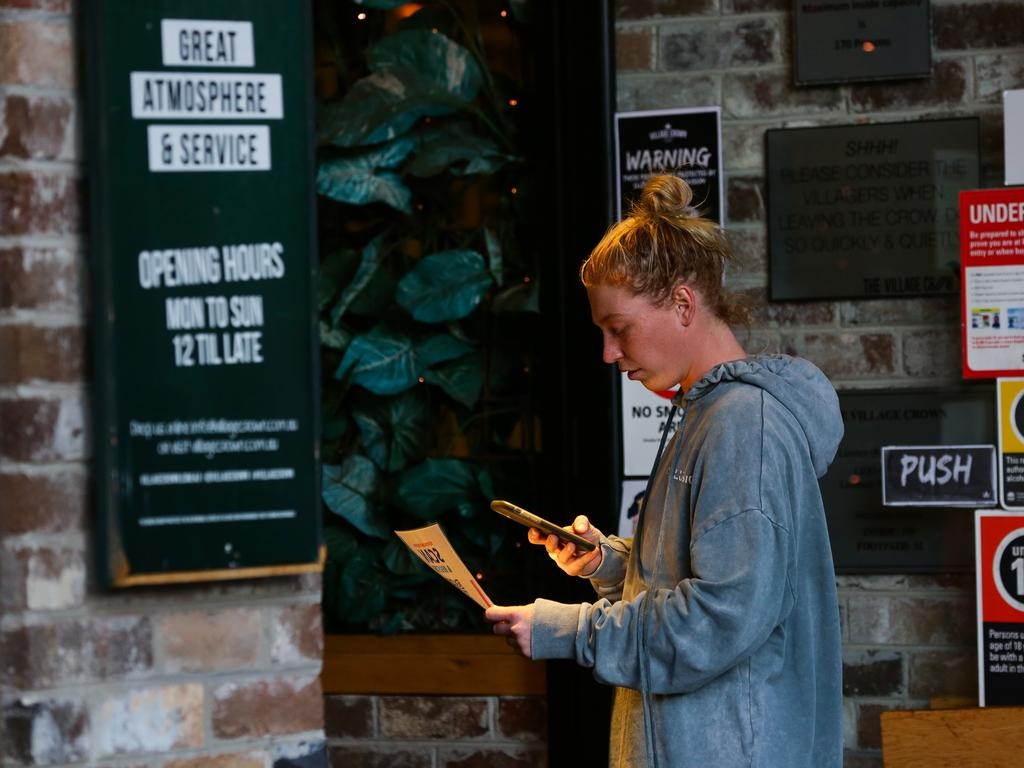 A young woman scans the QR code to sign in at the Village Crow pub in Sydney's Zetland. Picture: NCA NewsWire/Gaye Gerard