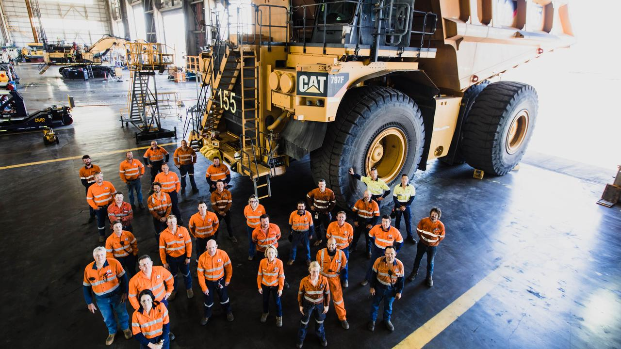 BMA employees with a Caterpillar truck. Picture: Nat Dixon