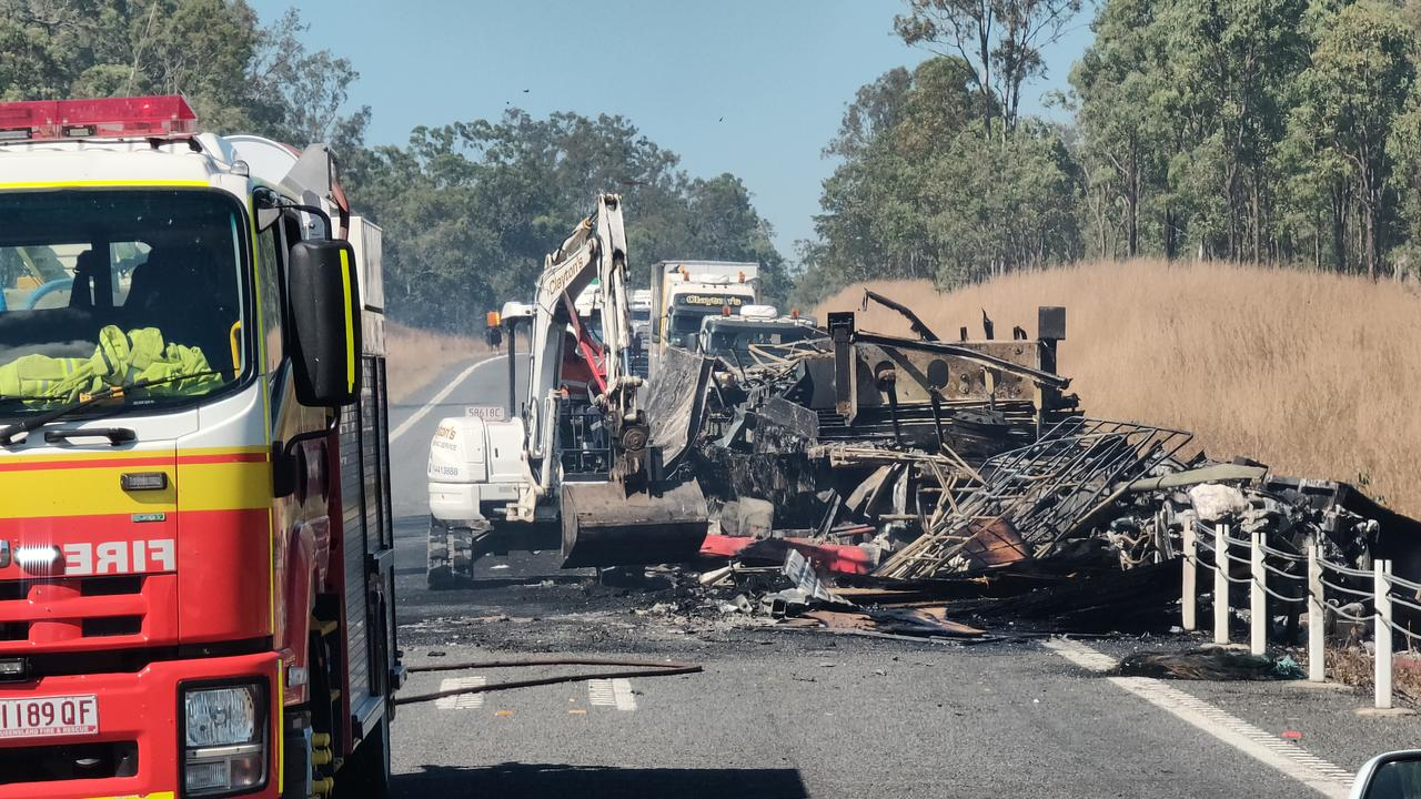Claytons towing use an excavator to clear the charred remains of a semi trailer sitting on the Bruce Highway, 37km south of Miriam Vale, after a two truck crash on August 5, at 11.15pm. Picture Rodney Stevens