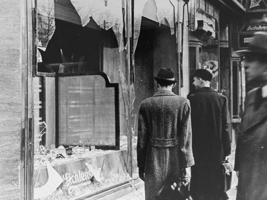 Germans pass by the broken shop window of a Jewish-owned business destroyed during Kristallnacht in Berlin. Picture: Supplied