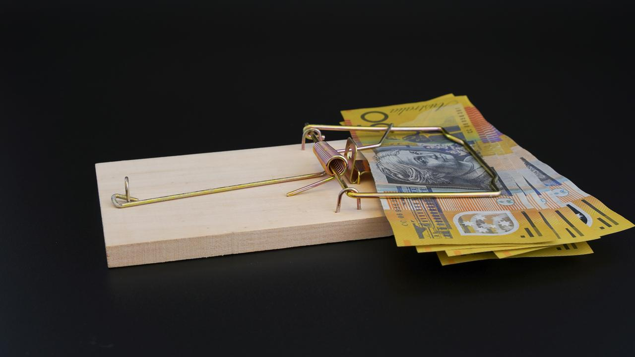 Rat trap on black background, trapping bank notes, conceptual use for business, risk, loans, financial trouble, with copy space. Australian money generic