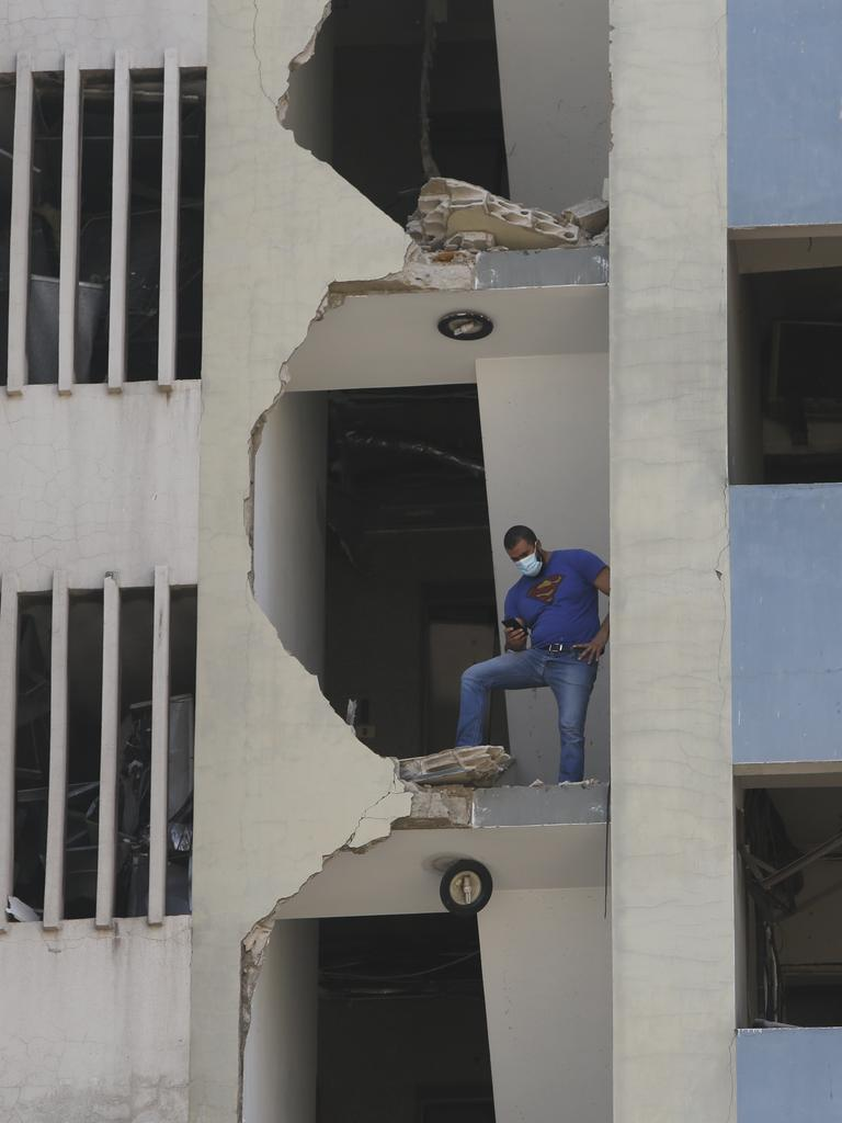 A man stands on the collapsed facade of a building. Picture: Marwan Tahtah/Getty