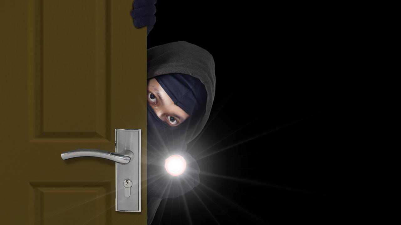 File photo of burglar sneaking in a open house door during a break and enter.