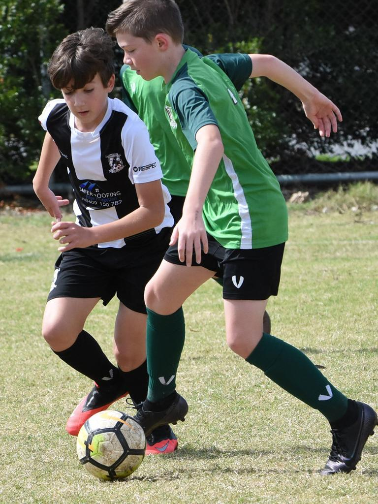 Under-12 footballers from Ipswich City and the Ipswich Knights work hard to control the ball in Saturday's match at Brassall. Picture: Gary Reid