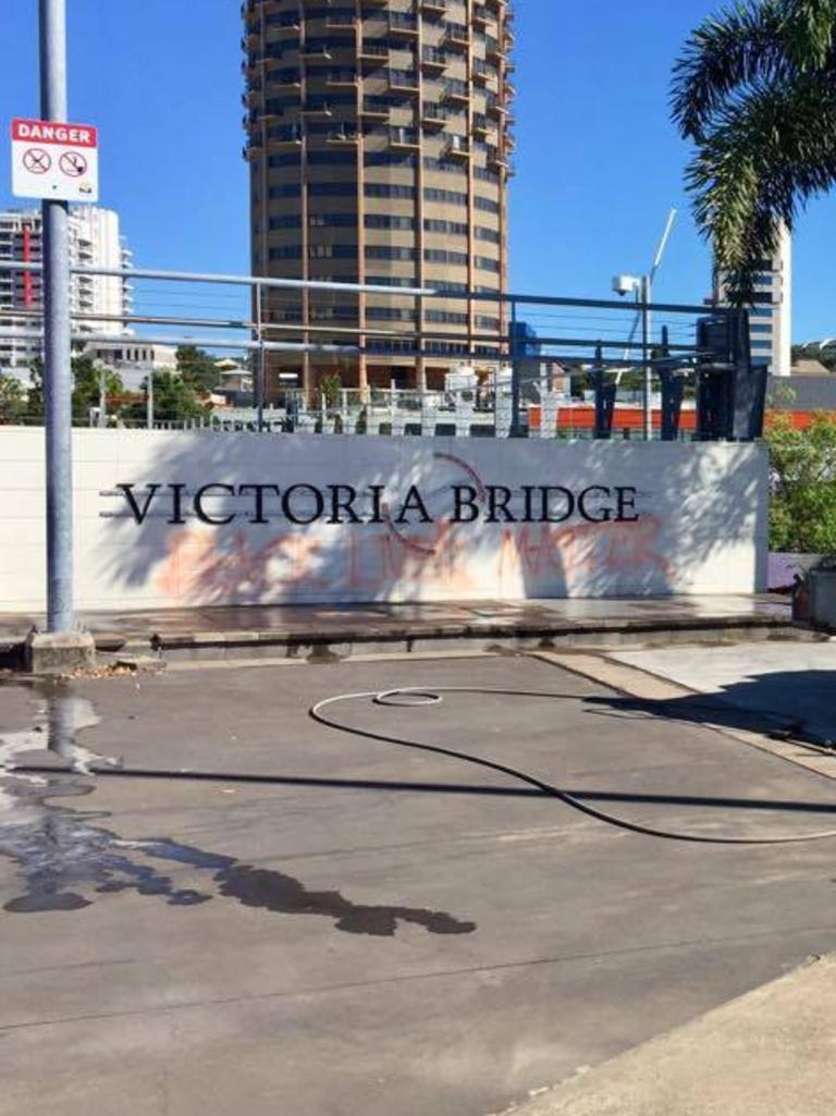 Townsville Council workers clean spray paint off the Victoria Bridge sign.
