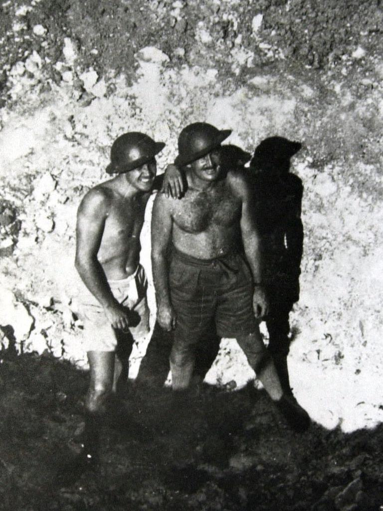 Naval officer Phil Chapman, left, poses with a mate in a bomb crater left by the attack on Darwin. File picture
