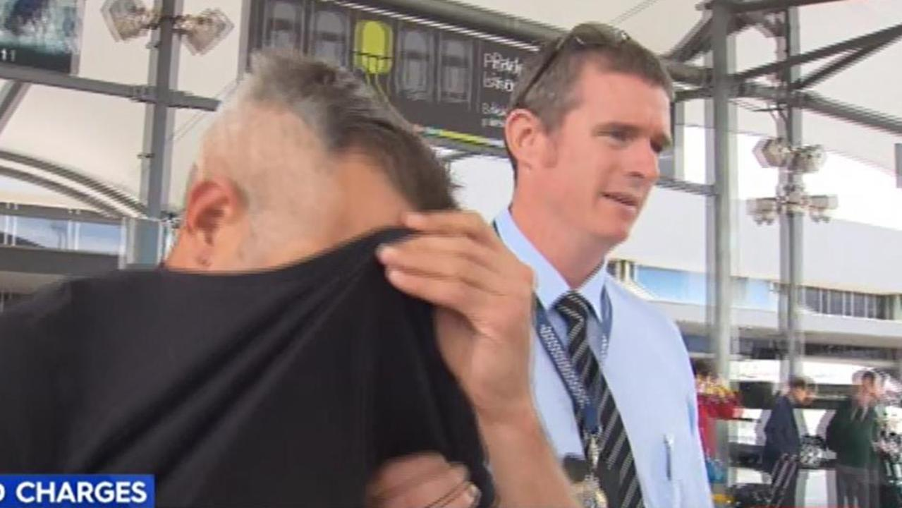 Tomas Novak covers his face at the Gold Coast Airport in 2017. Picture: Nine News