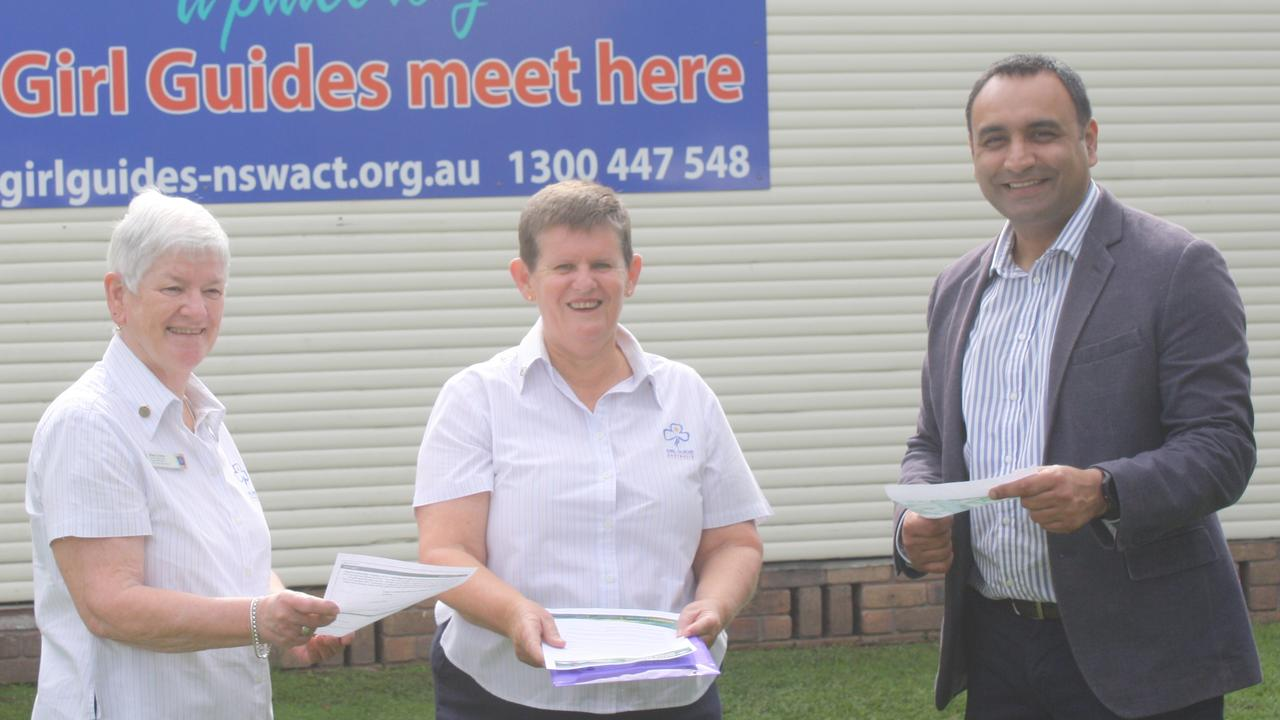 Coffs Harbour MP Gurmesh Singh examines important Girl Guide documents with North Pacific Coast Girl Guides region manager Elise Crofts and Coffs Harbour Girl Guides district manager Susan Gibson.