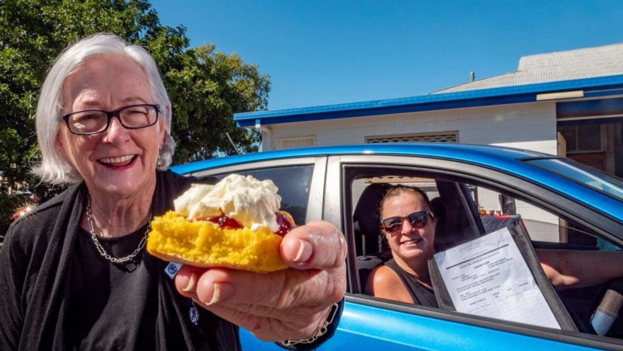 CAR SERVICE: QCWA Bundaberg president Lyn Tucker holds a delicious scone, as Geraldine Needham awaits to collect her order. Photo: ABC Wide Bay: Brad Marsellos.