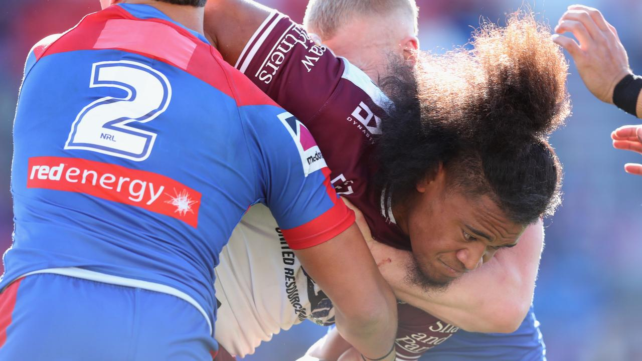 Moses Suli of the Manly Sea Eagles is tackled during the round 14 NRL match between the Newcastle Knights and the Manly Sea Eagles at McDonald Jones Stadium.