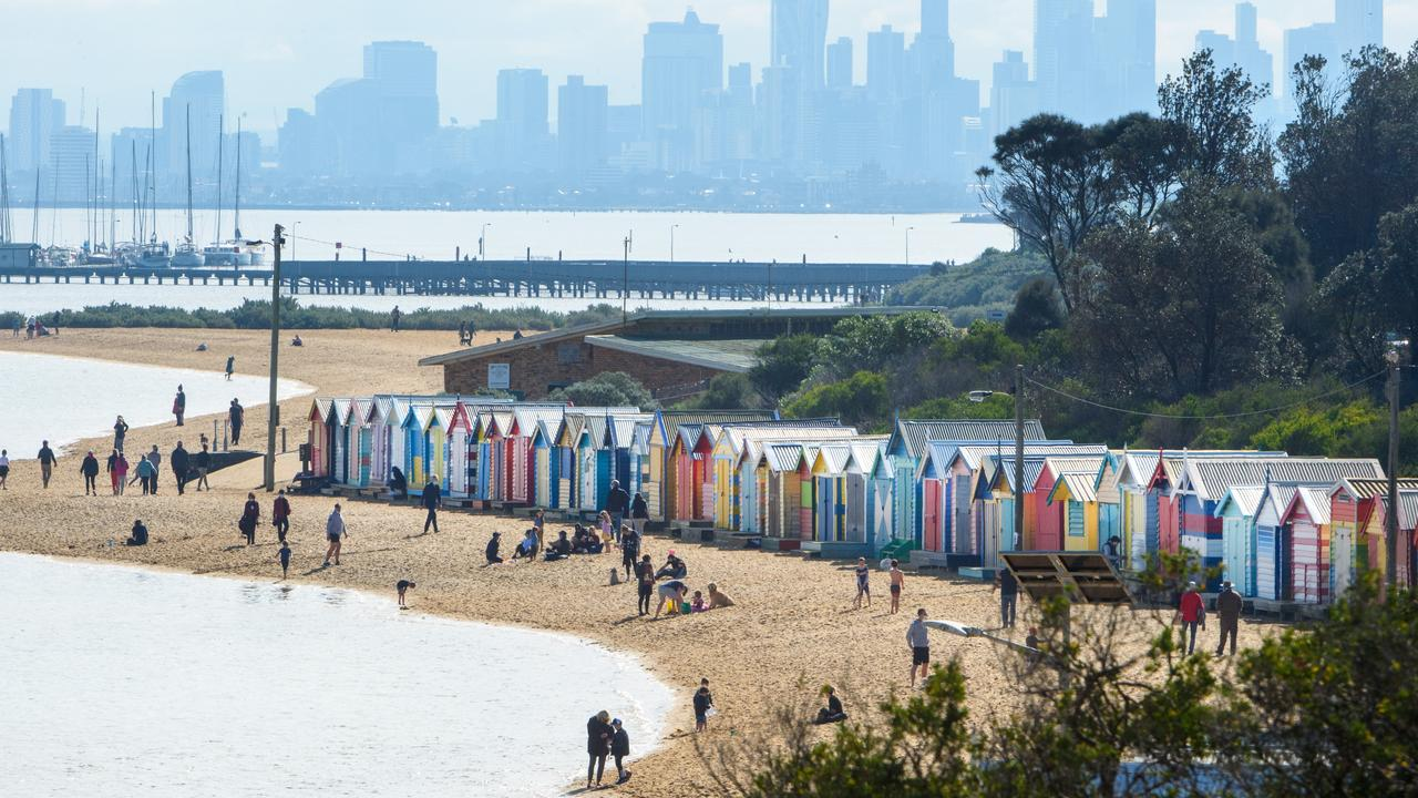 People sunbathing at Brighton Beach, which is not allowed under stage four restrictions. Picture: Jay Town