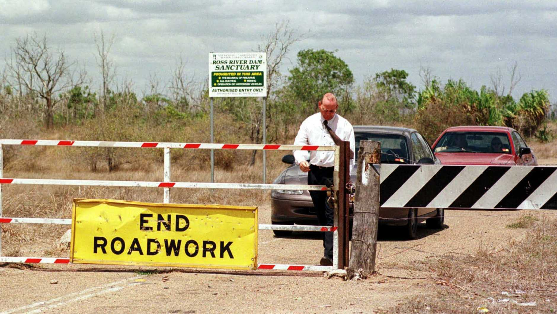 Sergeant Dave Hickey opens the gate for Judge Kerry Cullinane after looking at the Ant Hill (or Antill) Creek where the bodies of Townsville children Judith and Susan Mackay were found in 1970. Pic Steve Brennan. Queensland / Crime