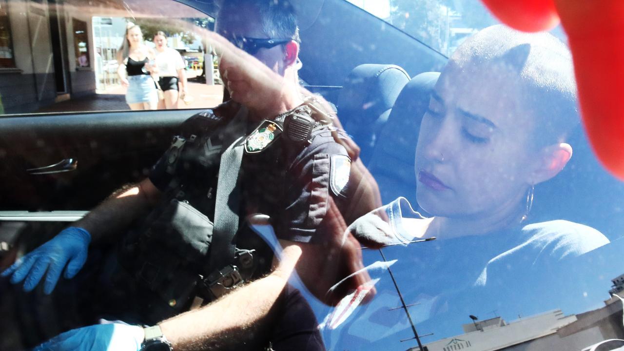 Cairns police officers arrest Madeleine Lewin in relation to the suspicious death of Brisbane man Anthony Brady, 52. PICTURE: BRENDAN RADKE