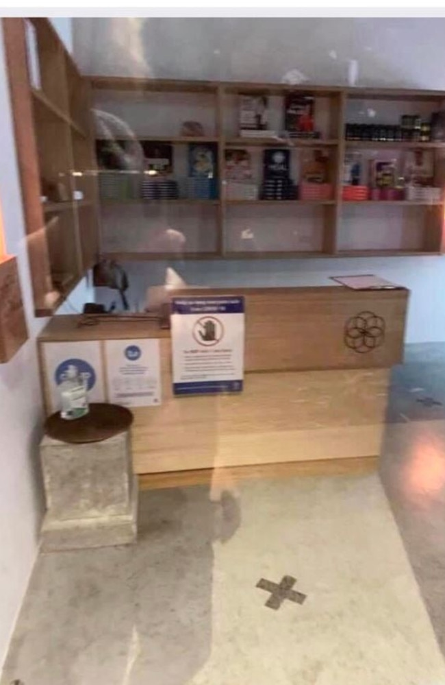 A photo taken through a window at the new Evolve Health Labs in Byron shows a COVID-19 safety sign and a hand sanitiser station. Picture: Supplied