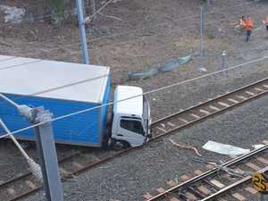 Trains suspended after truck crashes onto Brisbane line
