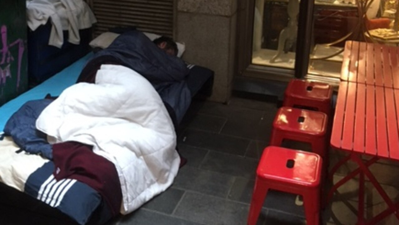 A rough sleeper sets up a camp bed in a laneway off Swanston St.