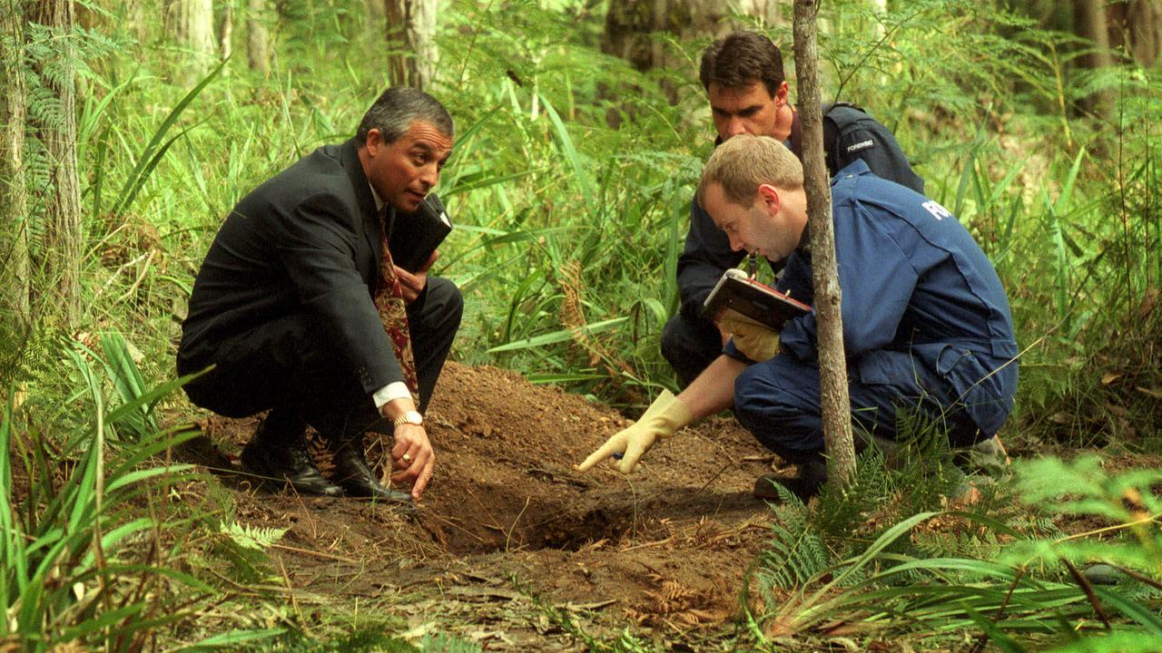 Homicide Detective Charlie Bezzine with forensic officers at double gravesite in Cambarville.
