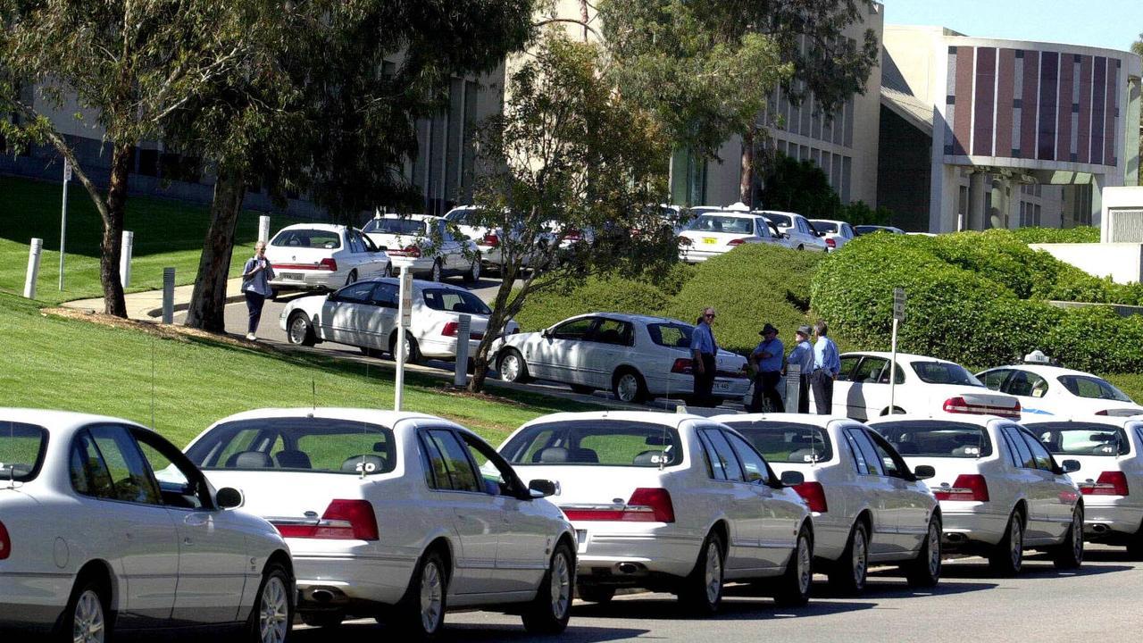 Senators' cars wait in a queue outside the Senate entrance at Parliament House in Canberra Pic John Feder.