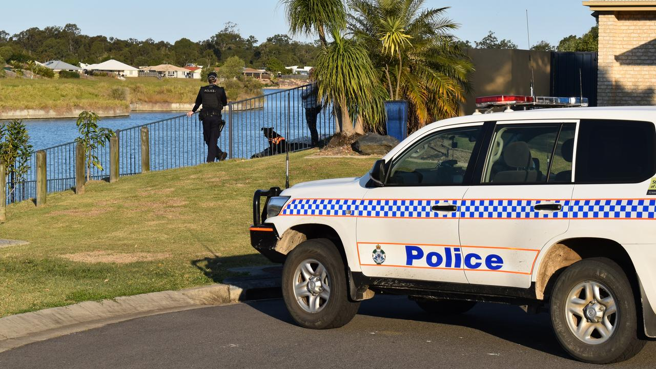 Police at the scene on Clearwater Cres, Toogoom, where a dead body was found in the lake.