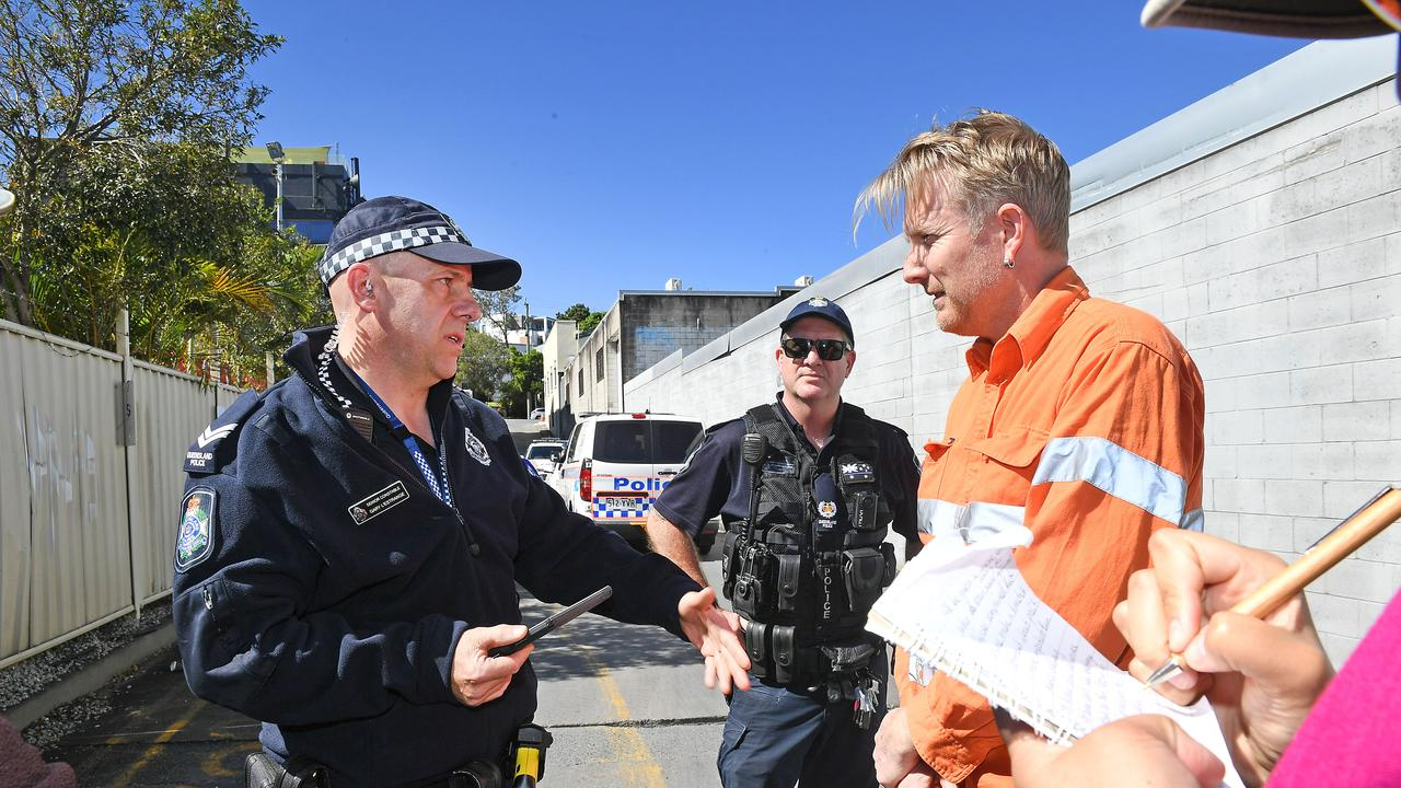 Ben Pennings getting told to move on by the Police. Protesters block trucks leaving the industrial site of an Adani contractor. Protesters blocking driveway as police move in to despursemove on. Friday August 9, 2019. (AAP image, John Gass)