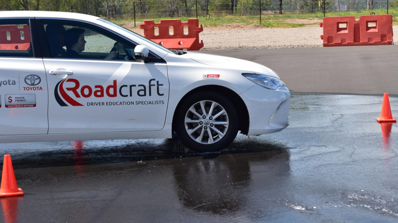 A participant in a driver education course at the Benaraby Driver Education facility practises wet curve braking techniques.