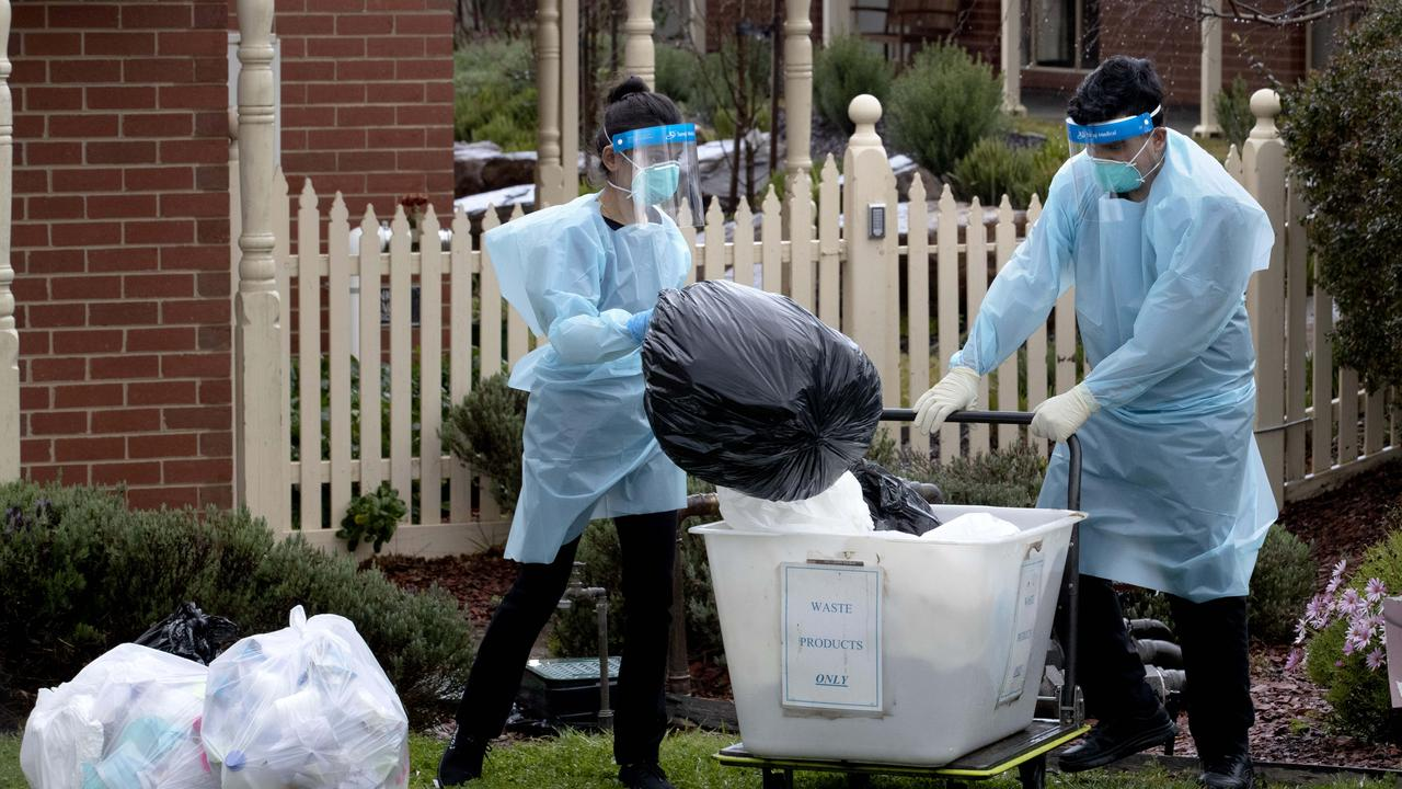 Staff in PPE remove waste at Japara Goonawarra Aged Care Home in Sunbury. The facility was one of many hit with a COVID-19 outbreak. Picture: David Geraghty