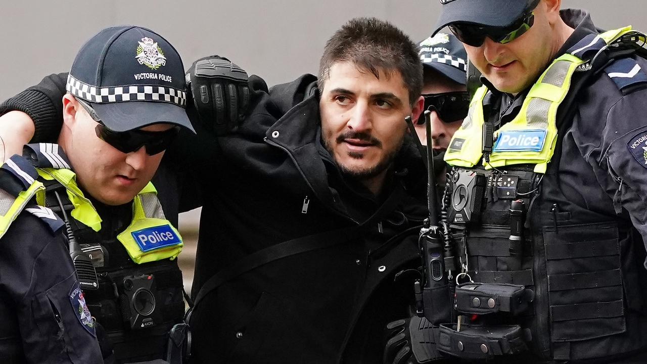 Fanos Panayides is detained by police officers as protesters gather outside Parliament House in Melbourne on May 10. Picture: AAP/Scott Barbour