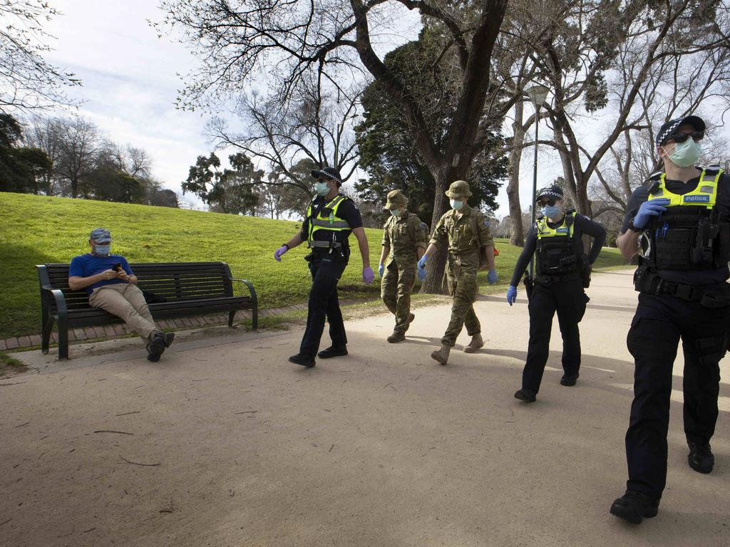 Police officers and army personnel patrol the Tan Track. Picture: NCA NewsWire / David Geraghty