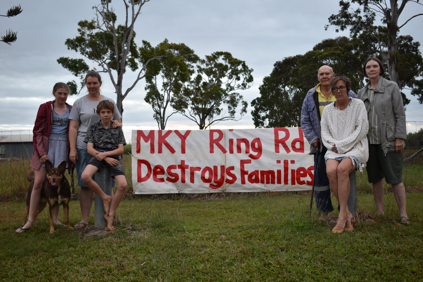 Christina Brown, 12, left, Mandy Brown, Joey Brown, 9, and Champ the red kelpie with James Schmidtke, Trudy Schmidtke and Terry Schmidtke near their sign protesting the Mackay Ring Road's opening.