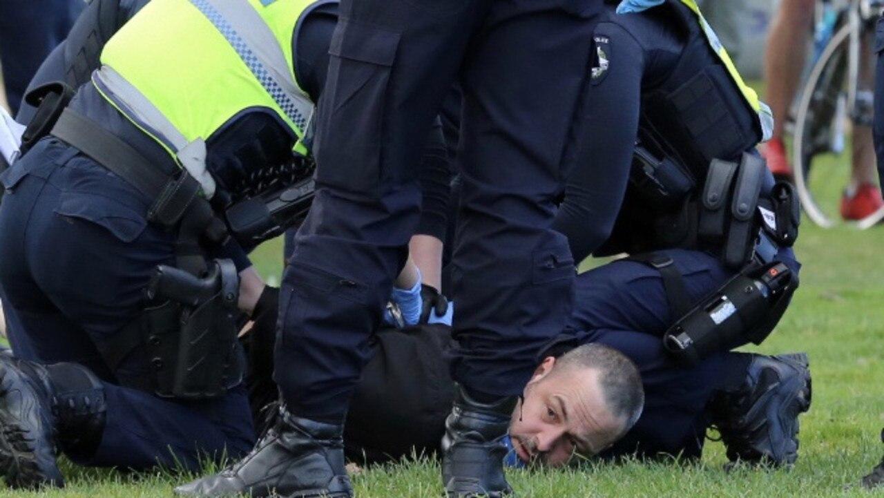 Police restrain a man at the scene. Picture: Matrix Media