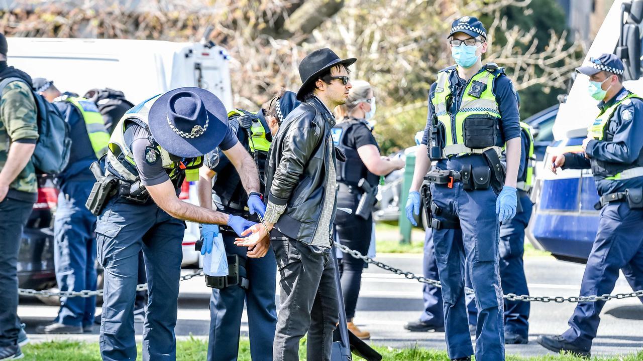 Police arrest a protester at Albert Park Lake. Picture: Jake Nowakowski