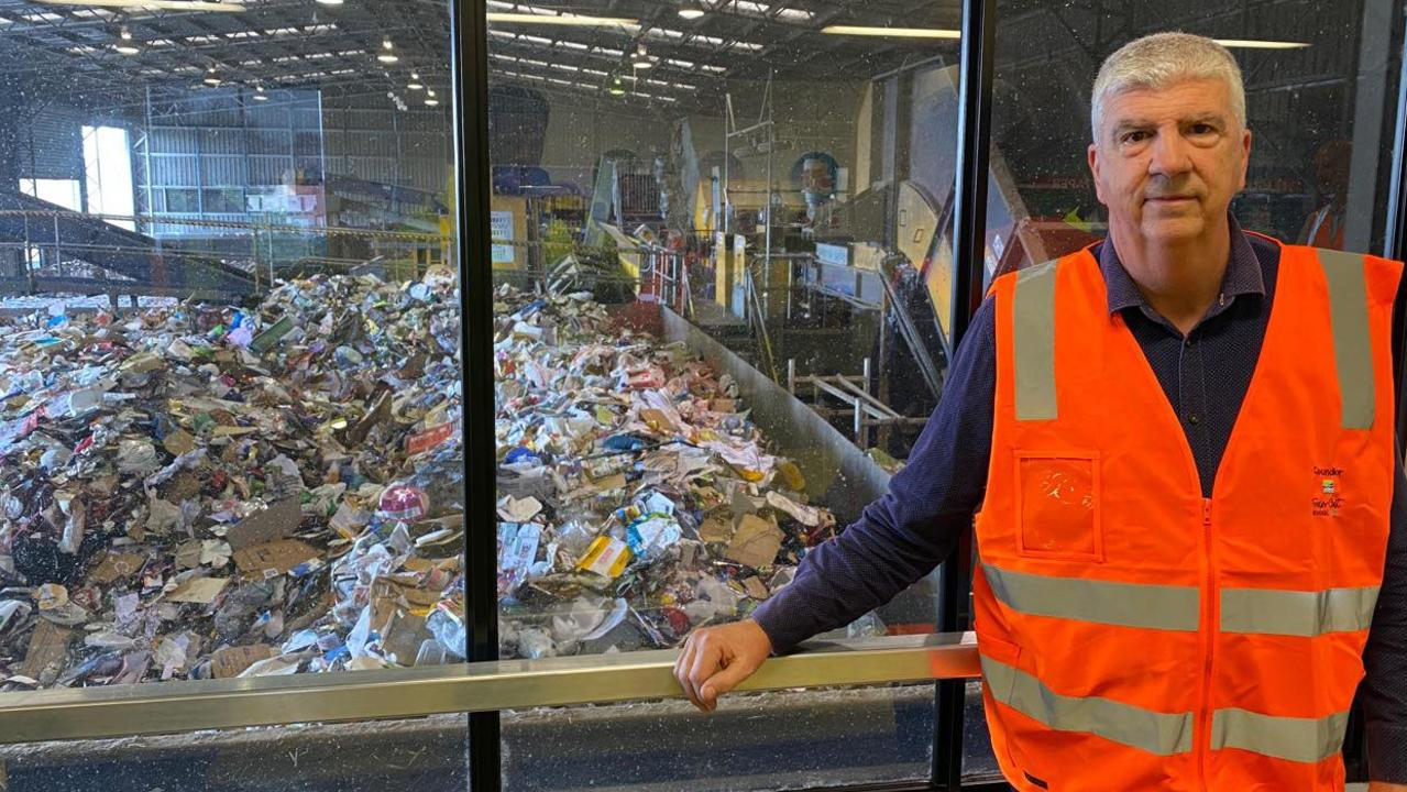 Councillor Phil Truscott standing in front of the rubbish at the Material Recovery Facility.