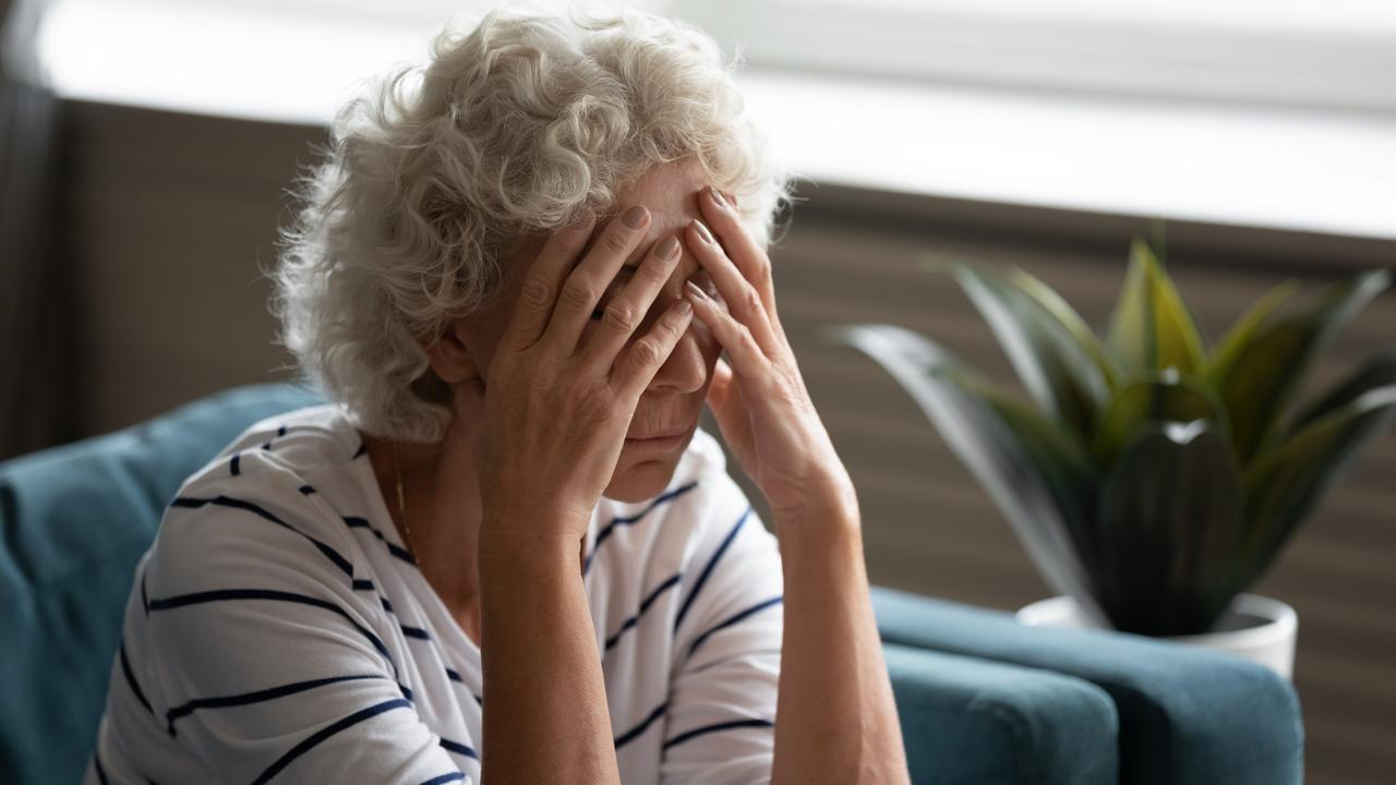 Close up 70s elderly woman sitting on sofa feels desperate crying. Picture iStock