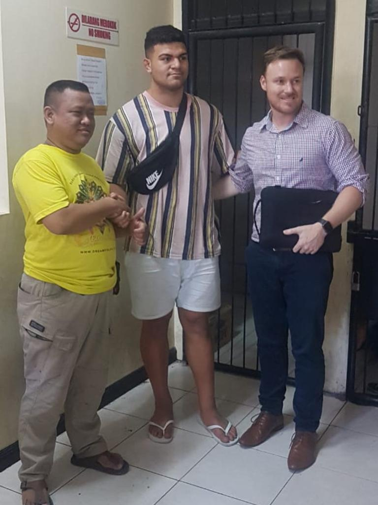 David Fifita shakes hands with the victim Dani Irawan and Broncos manager Adam Walsh inside Kuta Police Station.