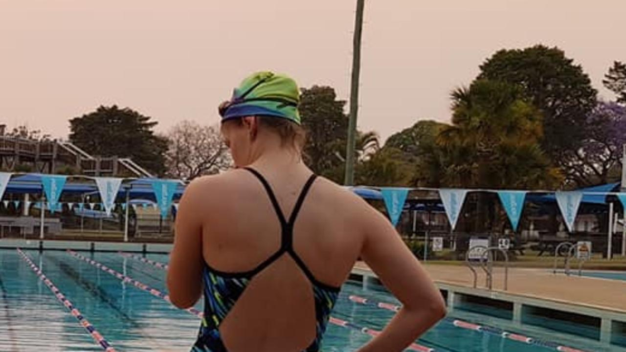 Grafton Services Swimming Club members hit the pool in Grafton under smokey skies from bushfires last year.