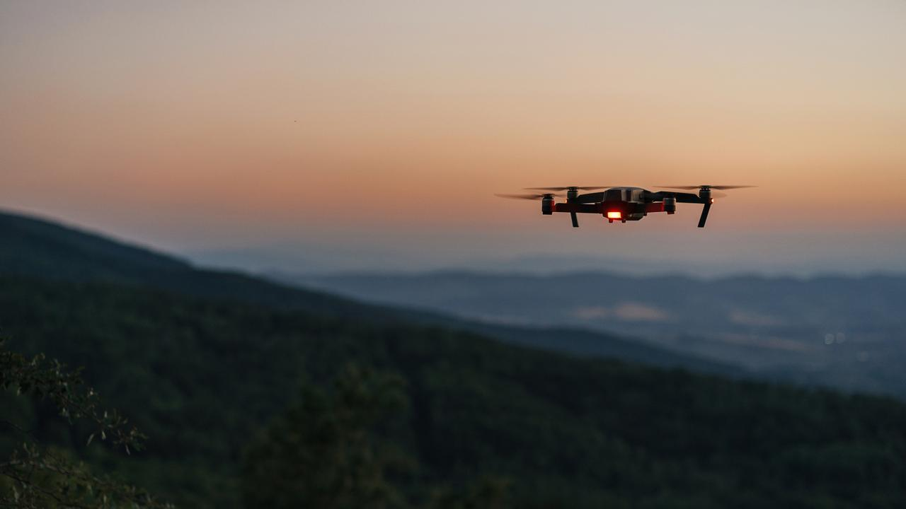 Drone flying over a mountain at dusk