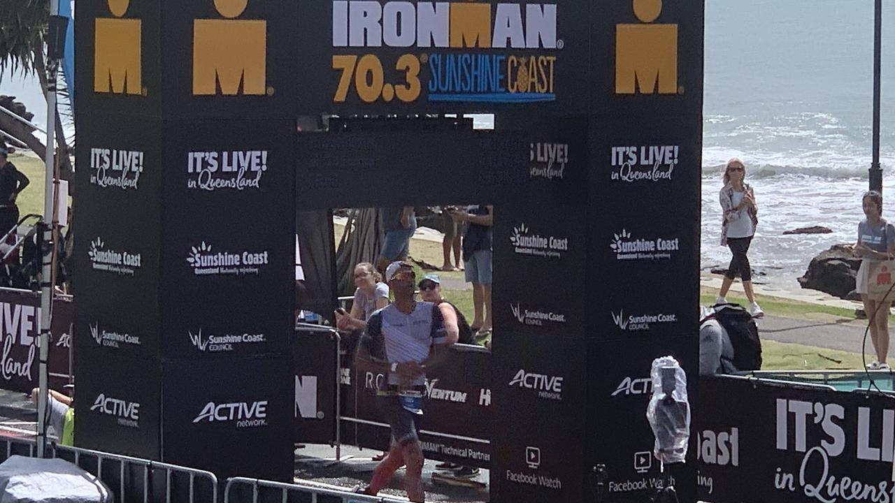 A finisher crosses the line in the Ironman 70.3 race at Mooloolaba. Picture: Matt Collins