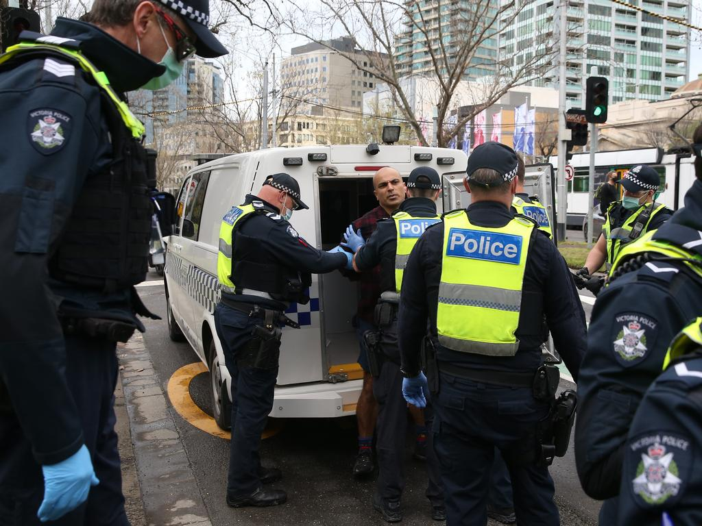 Police pictured making arrests at freedom protests in Melbourne on Saturday.