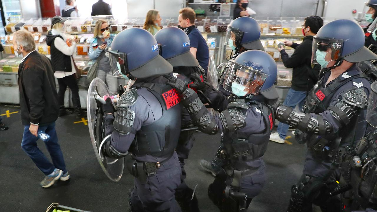 Police march past shoppers at the Queen Victoria Markets. Picture: David Crosling