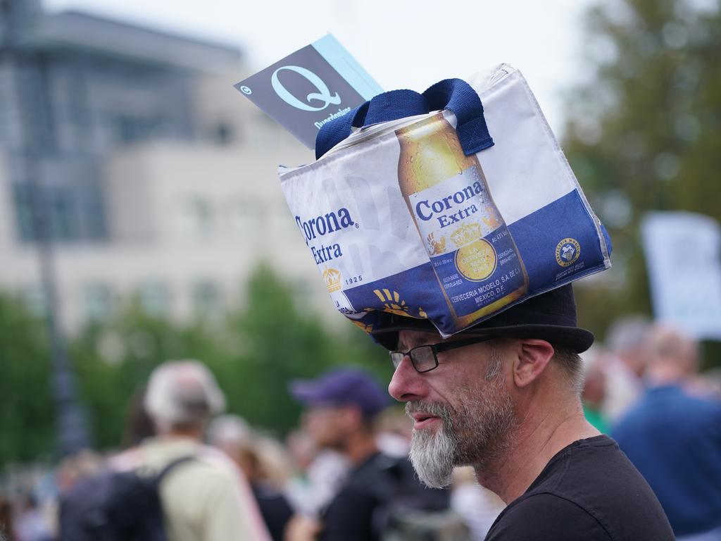A man wearing a Corona beer bag and a Querdenker Q flag attends a gathering of coronavirus sceptics in Berlin. Picture: Sean Gallup/Getty Images