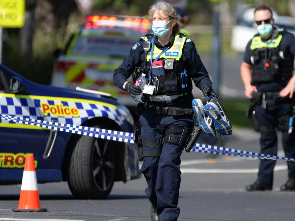 An officer holds a pair of shoes as police gather evidence from the crime scene. Picture: NCA NewsWire / Andrew Henshaw
