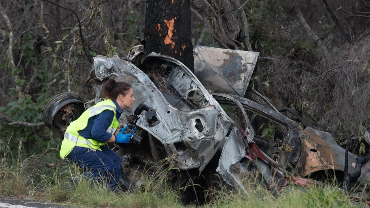 Police and emergency services look over the burned out wreckage of a car where the driver died after it hit a tree and caught fire west of Iluka. Photo: Adam Hourigan