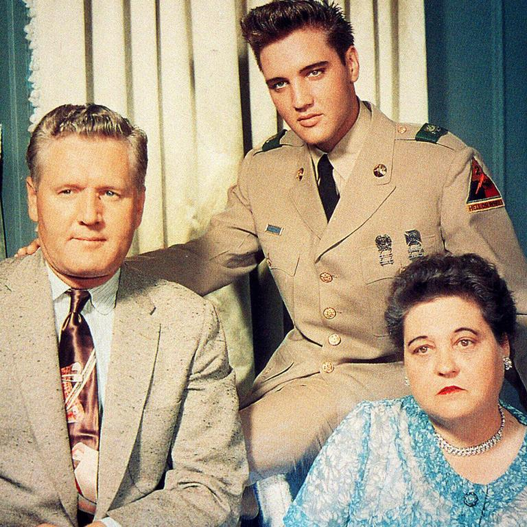 Elvis Presley dress in his US Army uniform with his father Vernon and mother Gladys.