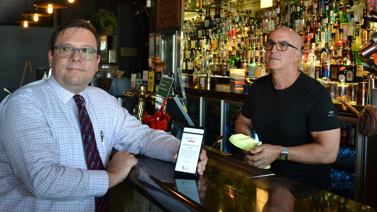 Townsville Chamber of Commerce president Michele Falconieri shows the safevisit contact tracing tool on his phone. He is with Heritage Exchange bar owner Emmanuel Bogiatzis who is using the tool but wants restrictions eased.